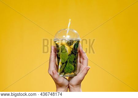Young Woman Hand Holding A Glass Of Cocktail With Mint. Studio Photo With Yellow Background.