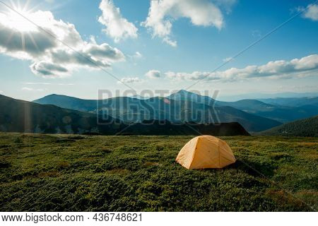 View Of Tourist Tent In Mountains At Sunrise Or Sunset. Camping Background. Adventure Travel Active