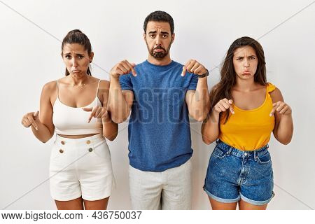 Group of young hispanic people standing over isolated background pointing down looking sad and upset, indicating direction with fingers, unhappy and depressed.