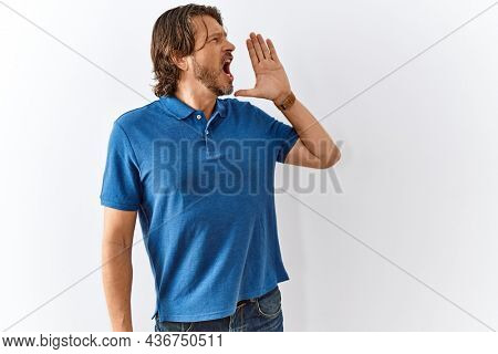 Handsome middle age man standing together over isolated background shouting and screaming loud to side with hand on mouth. communication concept.