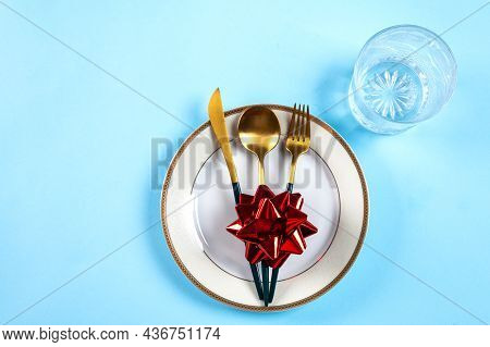 Christmas Table Setting With Modern Dishware And Decorations On Blue Background. Top View. New Year