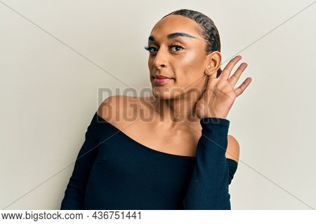 Hispanic man wearing make up and long hair wearing woman fashion clothes smiling with hand over ear listening and hearing to rumor or gossip. deafness concept.