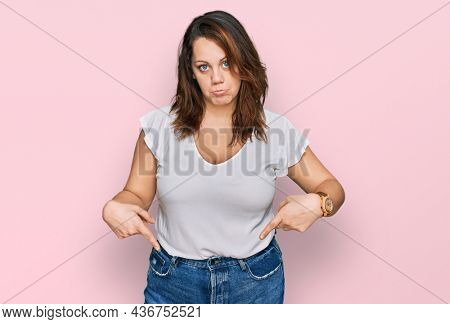 Young plus size woman wearing casual white t shirt pointing down looking sad and upset, indicating direction with fingers, unhappy and depressed.