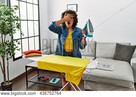 Young hispanic woman ironing clothes at home peeking in shock covering face and eyes with hand, looking through fingers with embarrassed expression.