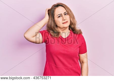 Middle age caucasian woman wearing casual clothes confuse and wondering about question. uncertain with doubt, thinking with hand on head. pensive concept.