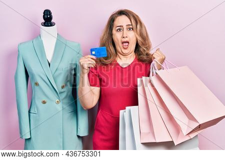 Middle age caucasian woman holding shopping bags and credit card in shock face, looking skeptical and sarcastic, surprised with open mouth