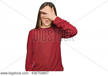 Beautiful brunette little girl wearing casual sweater peeking in shock covering face and eyes with hand, looking through fingers with embarrassed expression.