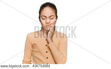 Beautiful brunette little girl wearing casual sweater touching mouth with hand with painful expression because of toothache or dental illness on teeth. dentist