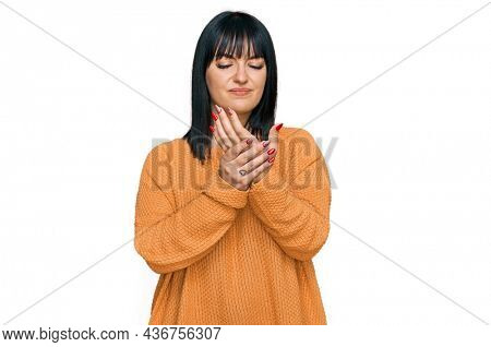 Young hispanic woman wearing casual clothes suffering pain on hands and fingers, arthritis inflammation