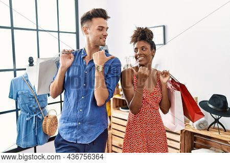 Young interracial couple holding shopping bags at retail shop smiling with happy face looking and pointing to the side with thumb up.