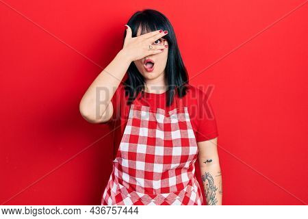 Young hispanic woman wearing cook apron and glasses peeking in shock covering face and eyes with hand, looking through fingers with embarrassed expression.