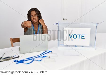 Young african american woman working at political election sitting by ballot punching fist to fight, aggressive and angry attack, threat and violence