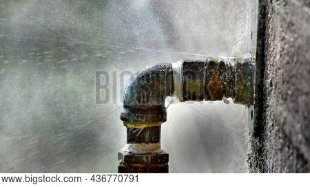 Old rusty pipe with leak and water spraying out under pressure leaky leaking