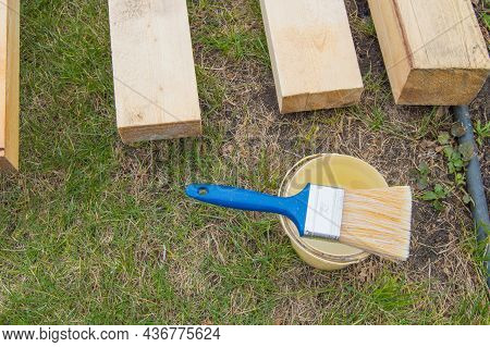 Preparation For Painting New Wooden Boards Lying On The Grass, A Paint Brush With A Bucket.