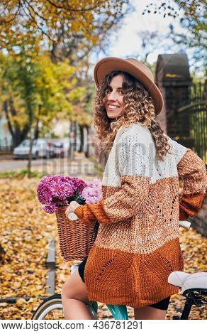 Back View Of Joyful Curly Female Cyclist In Knit Sweater With Basket Of Flowers Enjoying Bicycling A