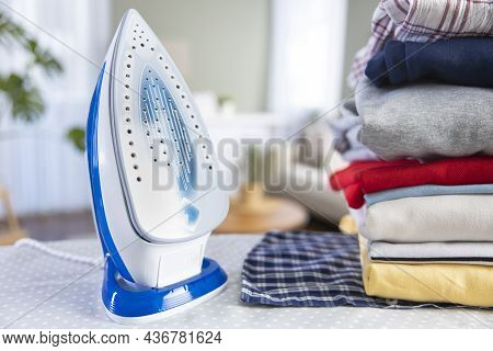 Iron And Folded Clean Clothes Standing On The Ironing Board