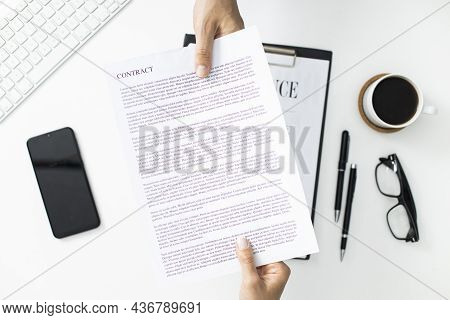 Businessman And Businesswoman Are Exchanging Contract Or Document. Office Table Top View
