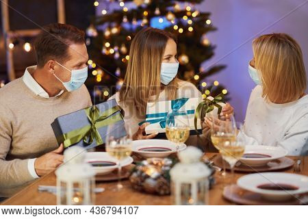 Friends celebrating christmas party wearing mask.