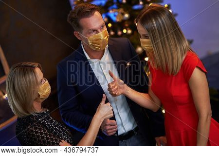 Business friends celebrating christmas party wearing masks