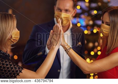 Business friends celebrating christmas party wearing masks. High quality photo