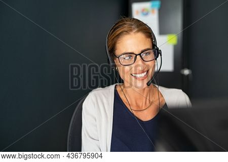 Call centre operator with headset on support hotline working from home. Mature positive agent in conversation with customer over headset. Happy middle aged businesswoman talking in a conference call.