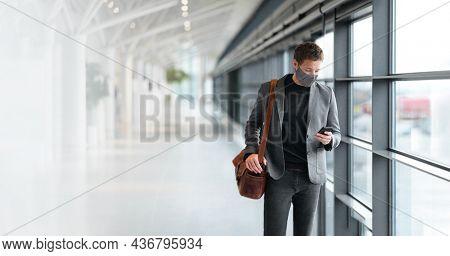 Travel business man wearing coronavirus face mask walking in airport using vaccine passport mobile phone app. Business travel professional people wearing face mask walking. technology coronavirus.