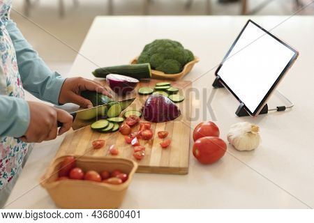 Hands of african american woman using tablet with copy space and cutting vegetables in kitchen. cooking, lifestyle and spending time at home with technology.