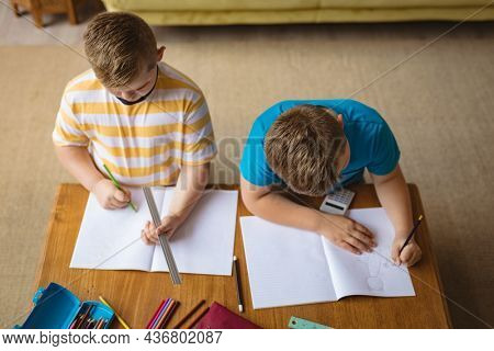 Overhead view of two caucasian boys drawing in their books sitting in the living room at home. childhood and hobby concept