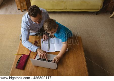 Overhead view of caucasian father using laptop to help his son with homework at home. home schooling and education concept