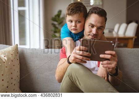 Caucasian father and son using digital tablet on the couch at home. fatherhood, technology and home concept