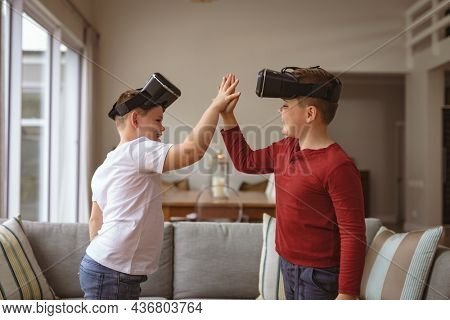 Two caucasian boys wearing vr headsets high fiving each others at home. gaming and entertainment concept