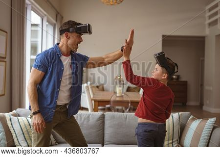 Caucasian father and son wearing vr headsets high fiving each others at home. gaming and entertainment concept