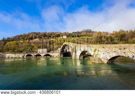 Italy, Lucca. The emerald cold water of the river reflects the ancient asymmetrical arches of the bridge. The bridge of Mary Magdalene crosses the Serchio River.