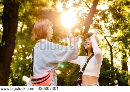 Multiracial two women smiling and giving high five while walking together in green park