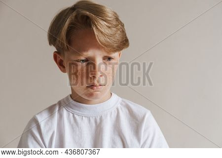 Portrait of an upset casual preteen boy in t-shirt standing over isolated gray wall background