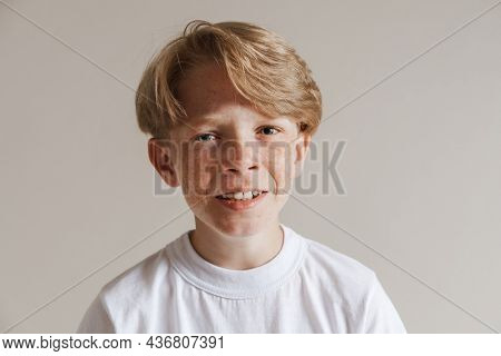 Portrait of an upset frowning casual preteen boy in t-shirt standing over isolated gray wall background crying