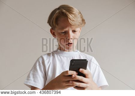 Portrait of a casual preteen boy in t-shirt standing over isolated gray wall background