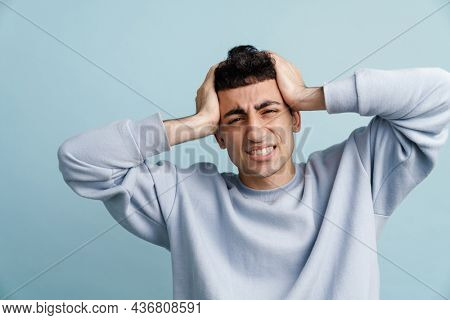 Young middle eastern man with headache holding his head isolated over blue background