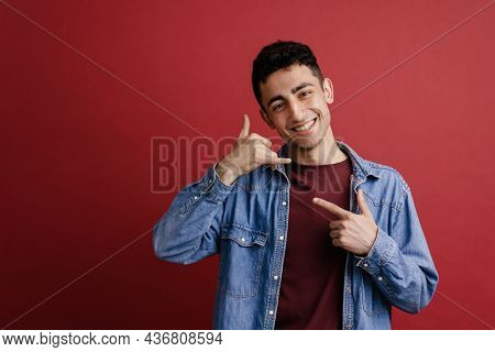 Young middle eastern man pointing finger at his handset gesture isolated over red background