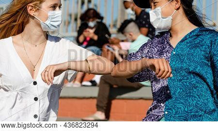 The new normal greeting elbow bump at an outdoors park