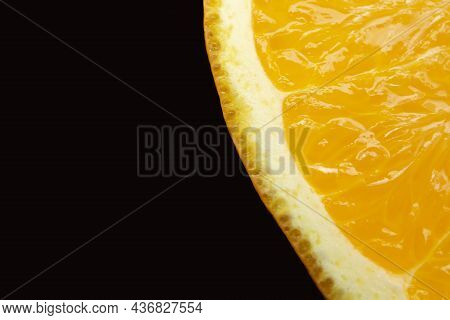 Part Of A Slice Of Juicy Orange In The Right Corner Of The Frame On A Black Background, Macro Photo.