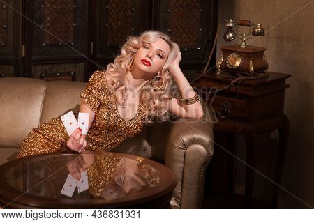 Pretty Young Woman Gambling On The Table. Blonde Model Wearing Gold Cocktail Dress. Gambling, Poker,