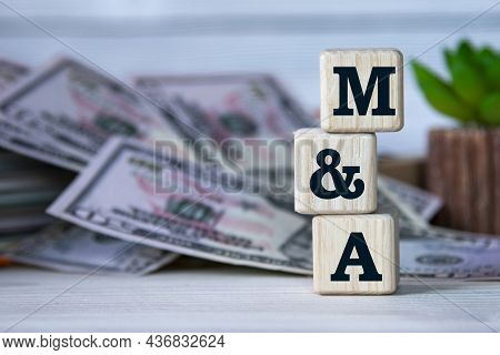 M And A (mergers And Acquisitions) - Acronym On Wooden Cubes On The Background Of A Cactus And Bankn