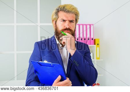 Confident Businessman In Office. Bearded Handsome Man With Notepad. Pensive Manager At Workplace.