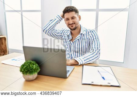 Young handsome man with beard working at the office using computer laptop confuse and wonder about question. uncertain with doubt, thinking with hand on head. pensive concept.