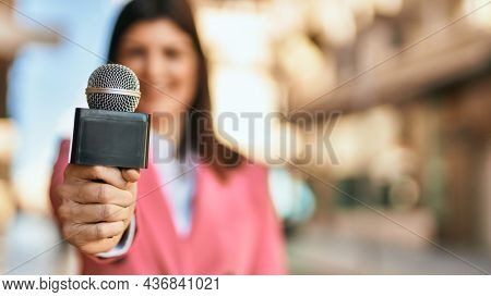 Middle age reporter woman holding journalist mic close to the camera, close up of professional microphone.