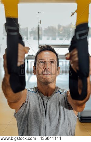 Man Does A Physical Exercise With Suspension Training Straps For Workout.
