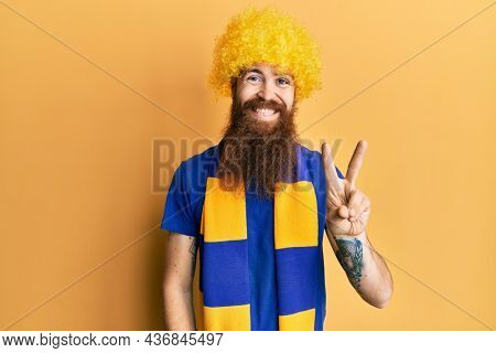 Redhead man with long beard football hooligan cheering game wearing funny wig showing and pointing up with fingers number two while smiling confident and happy.
