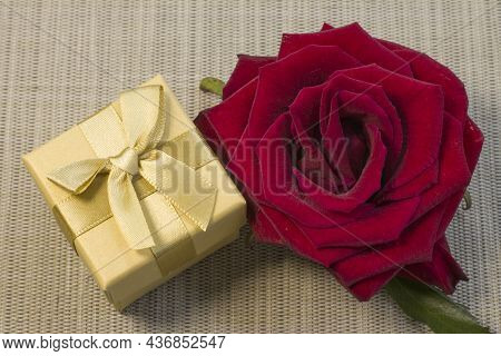 Gift Or Present Box Wrapped In Gold Paper And Rose Flower On Gray Table Top View. Flat Lay Styling C