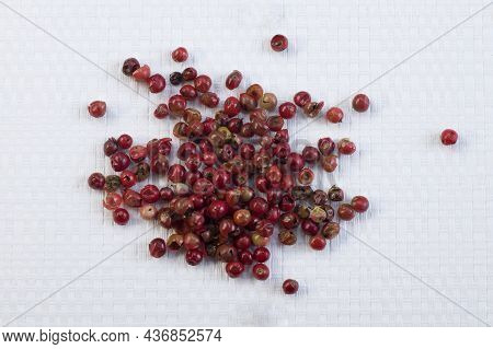 Red Or Pink Peppercorns On Light White Textured Cutting Board Background Top View